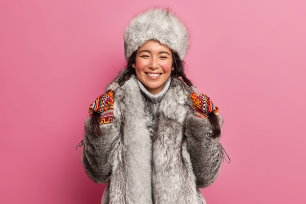 Alegre garota do norte segura duas tranças nas mãos, sorri e veste roupas de inverno se preparando para sair durante poses de dia frio contra a parede rosa do estúdio