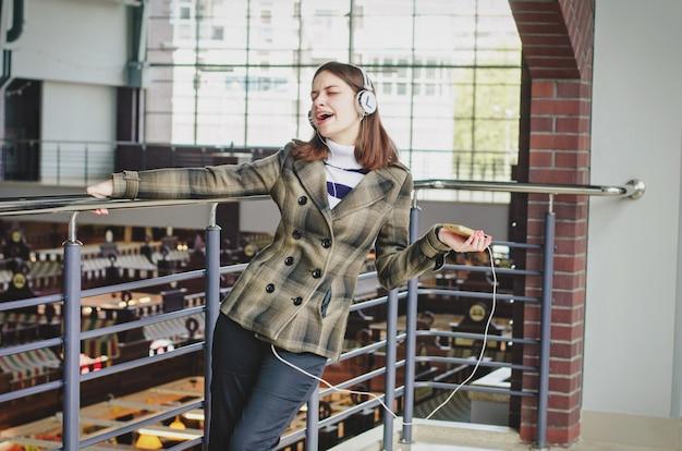 Alegre garota esbelta morena feliz em um shopping center se divertindo ouvindo música em fones de ouvido