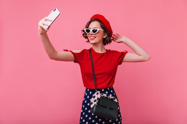 Alegre garota europeia com lindas tatuagens fazendo selfie. maravilhosa mulher francesa na boina e óculos de sol, tirando foto de si mesma.