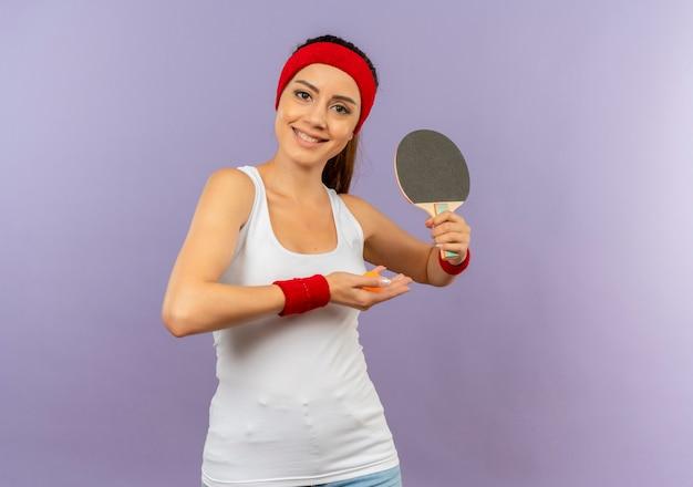 Alegre garota jovem fitness em roupas esportivas com bandana segurando a raquete e a bola de tênis de mesa com um sorriso no rosto em pé sobre a parede cinza