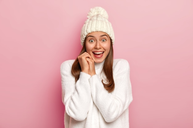 Alegre garota milenar de cabelos escuros tem uma reação feliz às boas notícias, sorri amplamente, usa um chapéu de inverno quente e um suéter branco confortável, tem um olhar entusiasmado, isolado na parede rosa
