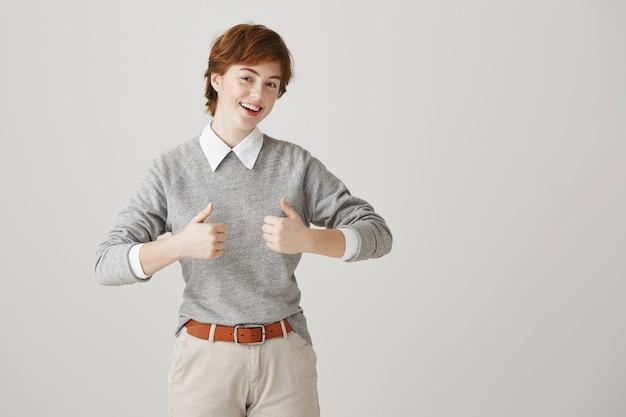 Alegre garota ruiva atraente com cabelo curto posando contra a parede branca