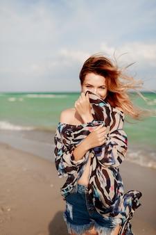 Alegre garota ruiva posando na praia ensolarada.