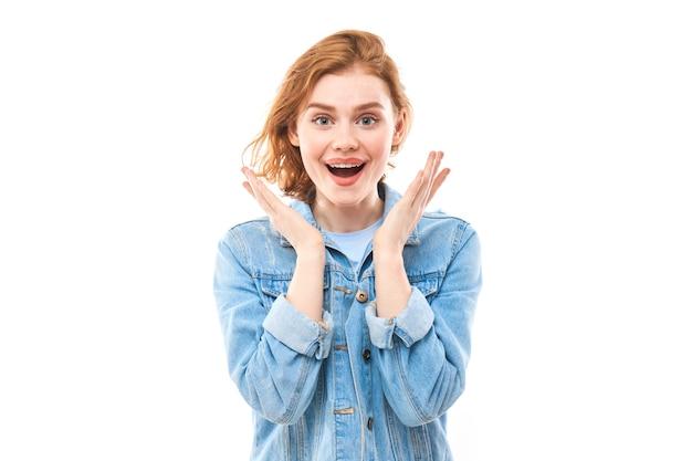 Alegre garota ruiva surpresa olha para a câmera. mulher jovem animada com um fundo branco e uma jaqueta jeans azul