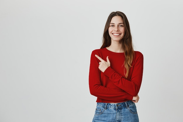 Alegre garota satisfeita sorrindo, apontando o dedo no canto superior esquerdo, recomendo