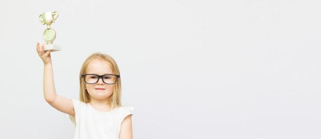 Alegre garotinha esperta comemorando a vitória isolada sobre fundo branco, usando óculos e mostrando um troféu