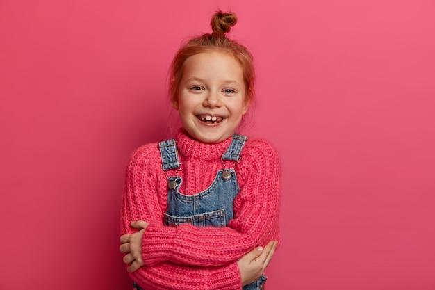 Alegre garotinha ruiva se abraça, se sente confortável, usa um suéter novo de lã rosa, roupa quente e macia, sorri com os dentes, mostra falta de dentes, tem cabelo ruivo, isolado na parede rosa.
