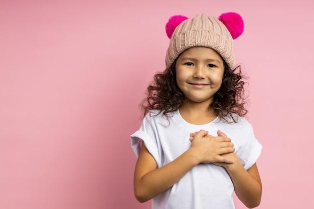 Alegre grata amigável caucasiana garotinha em camiseta branca, chapéu de malha bege, mantendo as duas mãos no peito, expressando gratidão, mostrando seu amor isolado.