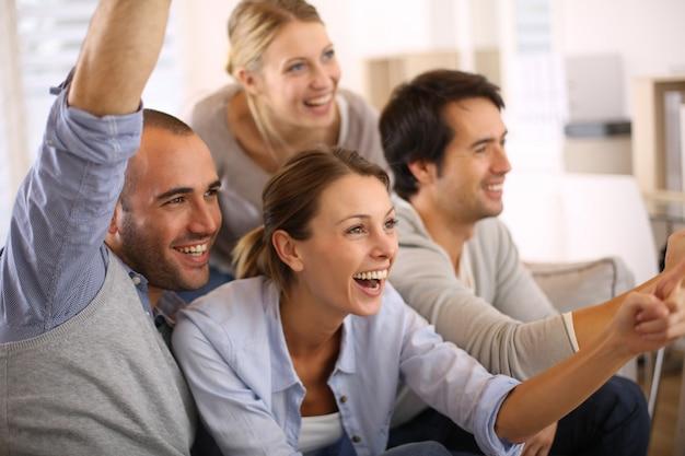 Alegre grupo de amigos assistindo jogo de futebol na tv
