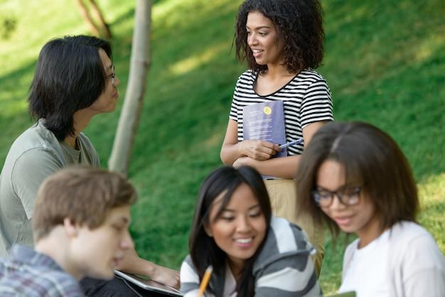 Alegre grupo de jovens estudantes sentados e estudando