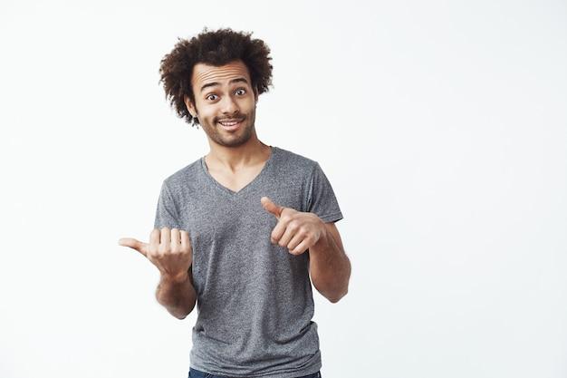 Alegre homem africano apontando os dedos no lado.