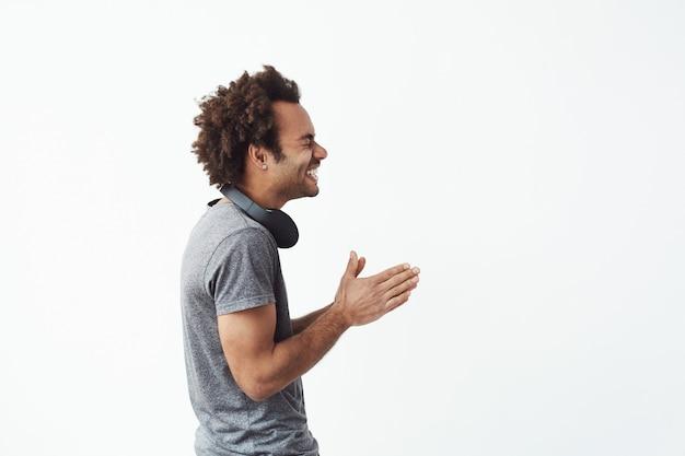 Alegre homem africano com fones de ouvido rindo em pé no perfil