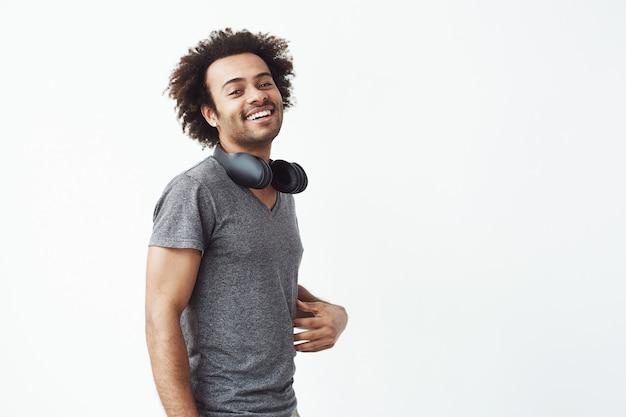 Alegre homem africano com fones de ouvido sorrindo
