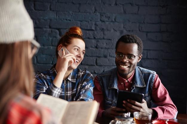 Alegre homem africano com tablet digital, jantar no café, juntamente com suas duas amigas: mulher de gengibre despreocupada, tendo uma boa conversa no celular