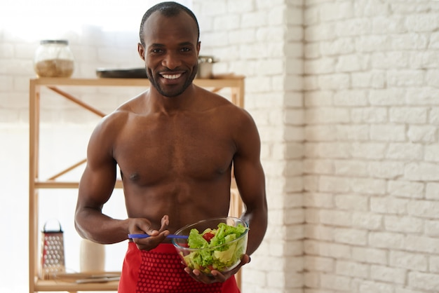 Alegre homem afro-americano agita salada na cozinha
