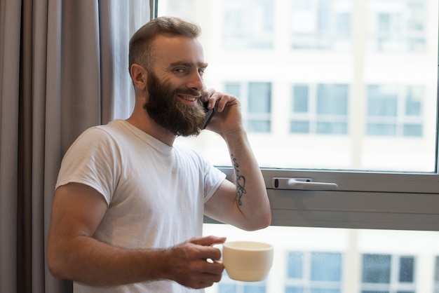 Alegre homem animado falando no telefone enquanto bebe café