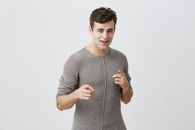 Alegre homem atraente em roupas casuais com corte de cabelo da moda e olhos azuis indica alegremente para você, escolhe competir, tem expressão positiva. modelo masculino em forma muscular considerável faz a escolha