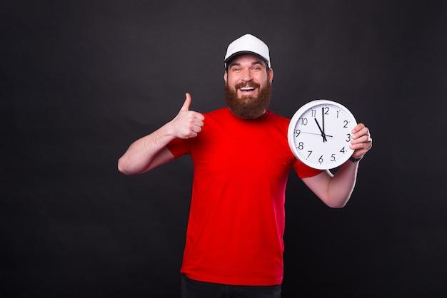 Alegre homem barbudo com camiseta vermelha mostrando o polegar para cima e segurando o relógio de parede às onze horas