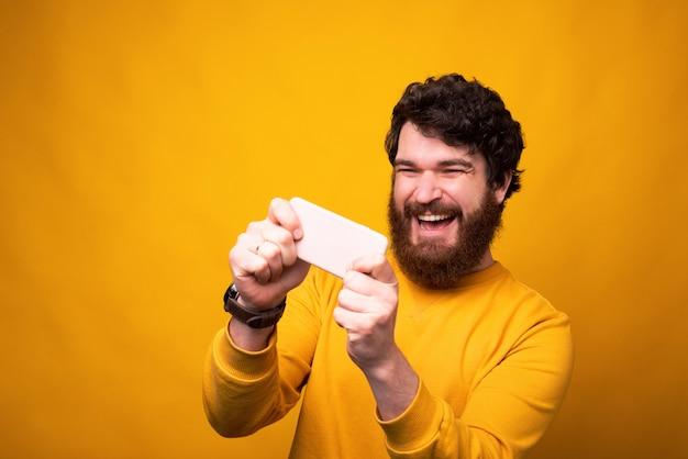 Alegre homem barbudo está jogando em seu telefone em fundo amarelo.