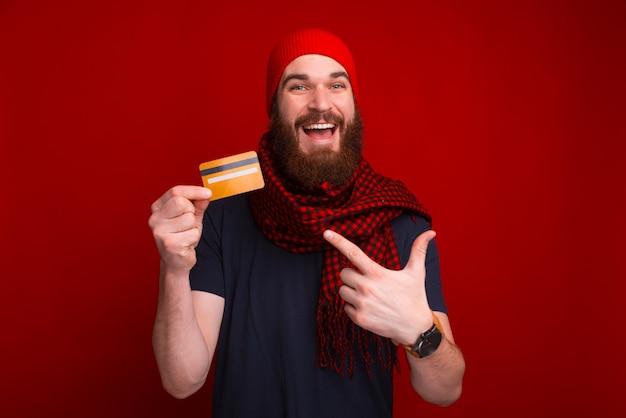 Alegre homem barbudo está mostrando e apontando um cartão de crédito perto da parede vermelha.