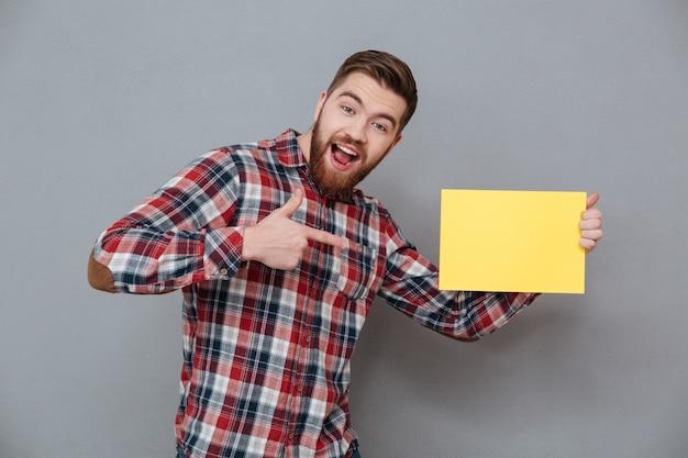 Alegre homem barbudo segurando papel em branco