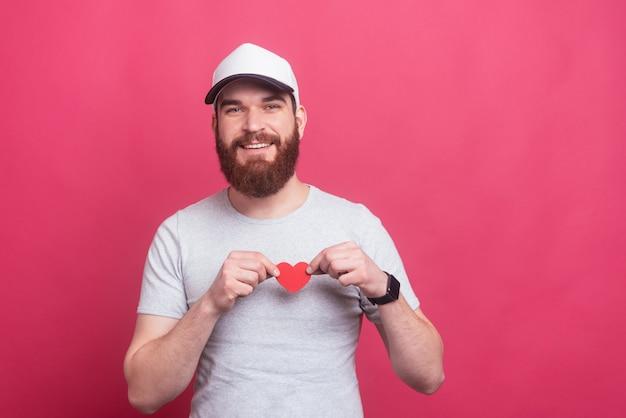 Alegre homem bonito segurando coração de papel vermelho sobre o peito