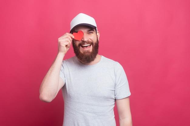 Alegre homem bonito segurando coração de papel vermelho sobre os olhos