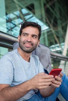 Alegre homem bonito segurando smartphone no aeroporto
