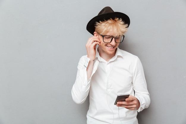 Alegre homem caucasiano usando óculos, ouvindo música