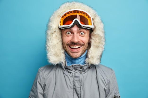 Alegre homem com a barba por fazer com sorrisos de expressão radiante, amplamente usa óculos de esqui, jaqueta de inverno com capuz e gosta de esportes de inverno extremo.