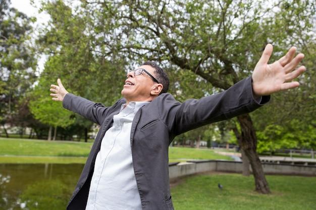 Alegre homem de meia idade, espalhando as mãos no parque