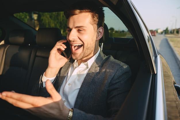 Alegre homem de terno clássico, falando no celular, enquanto volta sentado no carro da classe executiva