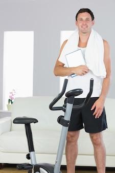 Alegre homem desportivo em pé atrás de bicicleta de exercício segurando o tablet