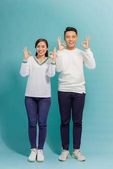 Alegre homem e mulher multinacional sorrindo e gesticulando sinal de ok isolado sobre o azul