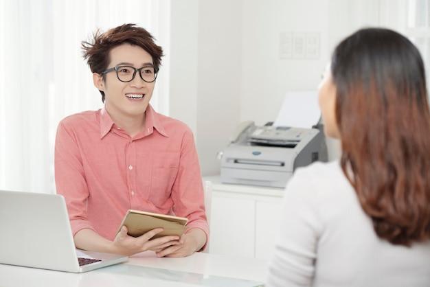 Alegre homem étnico com colega de trabalho na mesa