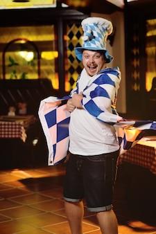 Alegre homem gordo com uma barriga grande com uma bandeira da oktoberfest e um chapéu da baviera
