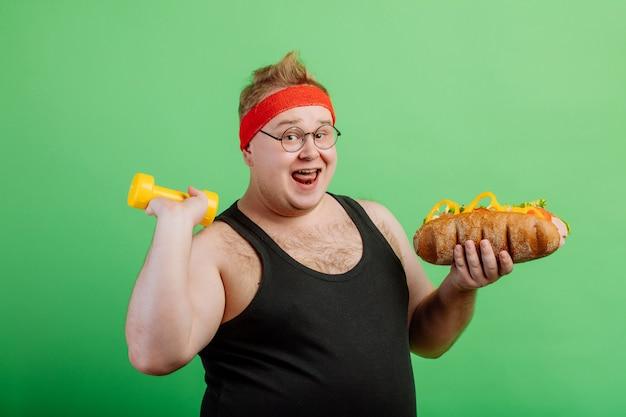Alegre homem gordo se divertindo com hambúrguer e halteres