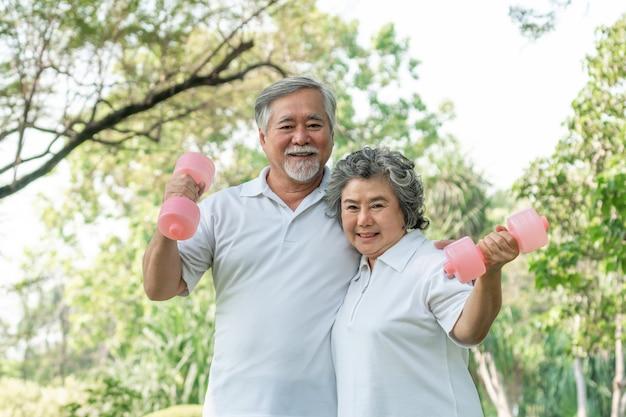 Alegre homem idoso e mulher sênior com halteres para treino no parque, eles sorrindo com bom e saudável juntos