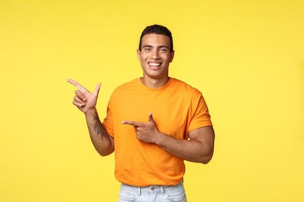 Alegre homem moderno com o braço tatuado, apontando para a esquerda como promoção da loja on-line, convidar convidados para participar da festa, sorrindo alegremente, recomendar tentar algo, dar conselhos que lugar visitar, fundo amarelo