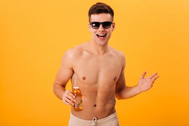 Alegre homem nu de bermuda e óculos escuros, segurando a garrafa de cerveja