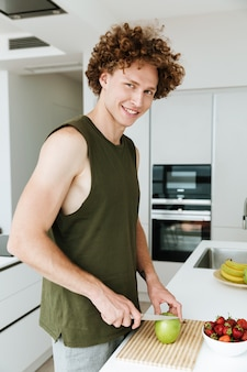 Alegre homem parado na cozinha e cozinhar