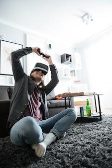 Alegre homem sentado em casa dentro de casa jogar jogos