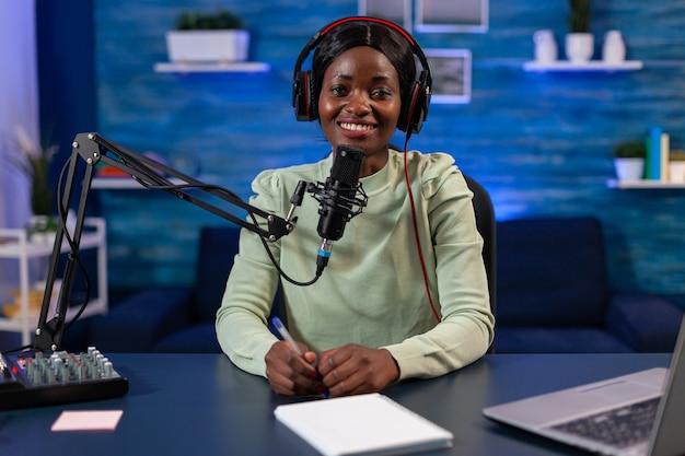 Alegre influenciador africano gravando podcast da internet de programa on-line em casa. falando durante a transmissão ao vivo, blogueiro discutindo no podcast usando fones de ouvido.