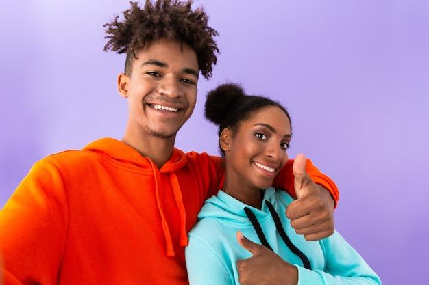 Alegre irmão e irmã juntos e mostrando os polegares para cima, isolados sobre a parede violeta