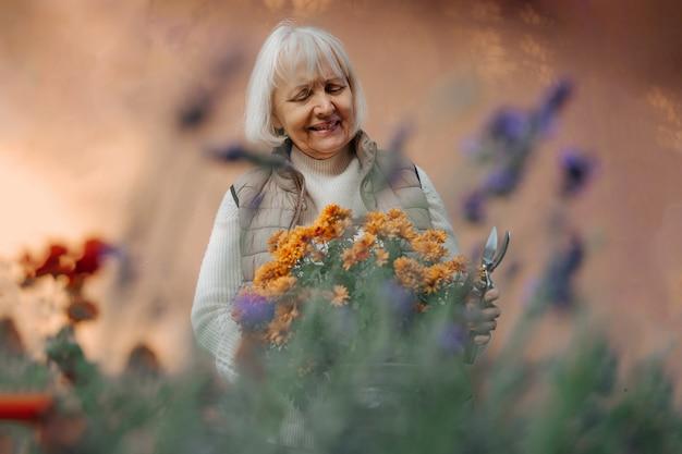 Alegre jardineira idosa sorrindo e cuidando de plantas florescendo