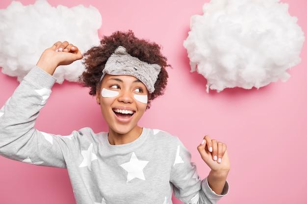 Alegre jovem adolescente étnica sorri amplamente, dança e se move ativamente, levanta os braços, tem bom humor pela manhã, usa roupas caseiras confortáveis, isolado sobre as nuvens de parede rosa acima