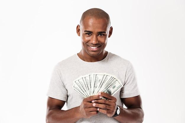 Alegre jovem africano segurando dinheiro