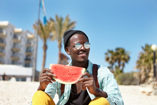 Alegre jovem afro-americano masculino vestido com roupas da moda, tendo um bom tempo ao ar livre à beira-mar, desfrutando de melancia suculenta e bom tempo ensolarado, sorrindo amplamente, admirando a bela vista do mar