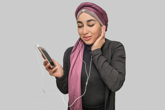 Alegre jovem árabe segurar telefone. ela ouve música através de fones de ouvido. modelo mantenha os olhos fechados.