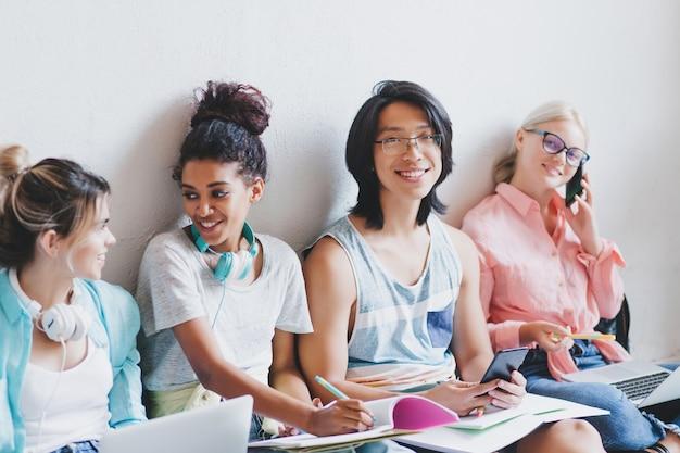 Alegre jovem asiático de óculos sorrindo enquanto sua amiga loira universitária falando ao telefone. garota muito encaracolada, escrevendo palestra no livro e contando algo para a irmã bonita.